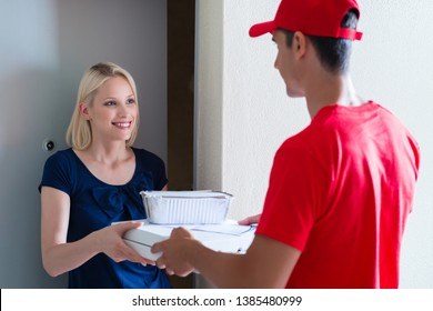 Smiling young female customer receiving the pizza order at door from delivery man