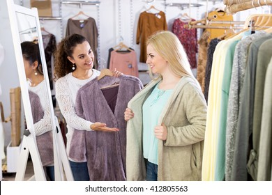 Smiling young female customers selecting coats and jackets at the shop. Focus on the right woman