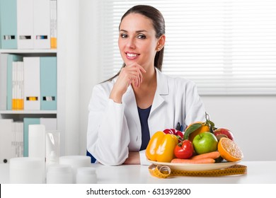 Smiling young Female Dietitian sitting at desk and showing colorful vegetables and fruit, healthy eating and diet concept