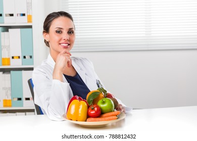 Smiling young Female Dietitian sitting at desk and showing colorful vegetables and fruit; healthy eating and diet concept