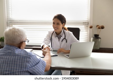 Smiling young female doctor shake hand of elderly male patient at consultation in private hospital. Happy positive woman GP handshake get acquainted or close health insurance deal with mature client.