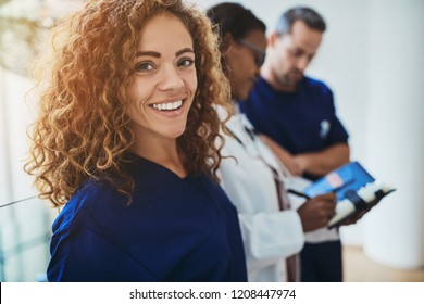 Smiling young female doctor standing in a hospital corridor with two medical colleagues talking in the background