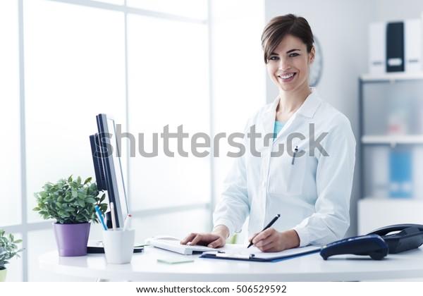 診療所のレセプションで働く若い女性医師に微笑みながら、彼女はコンピューターを使い、医療報告書を書いている