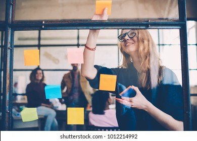 Smiling young female employee in stylish spectacles using stickers for creation strategy of working project during brainstorming session, skilled team member making notes presenting idea of startup