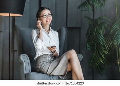 Smiling young female entrepreneur listening music on her cellphone while sitting in lobby of modern office building