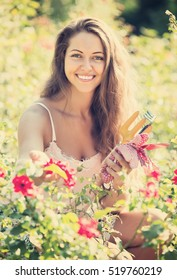 Smiling young female florist working in summer garden