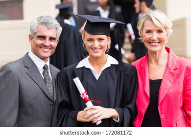 smiling young female graduate with parents at graduation ceremony