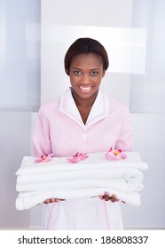 Smiling young female housekeeper carrying towels in hotel