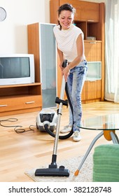 Smiling young female make cleaning at house using hoover