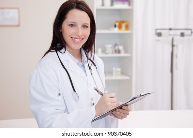 Smiling young female physician taking notes
