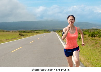 smiling young female runner going to countryside road running and carrying mobile phone using earphone listening music to train body.