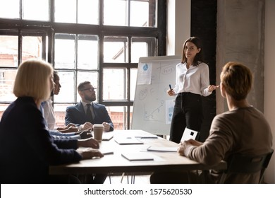Smiling young female speaker standing near flipchart with graphs diagrams, presenting market research results to focused diverse colleagues at brainstorming meeting or educational seminar in office.