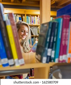 Smiling young female student reading book amid bookshelves in the college library