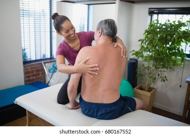 Smiling young female therapist examining back of shirtless senior male patient sitting on bed at hospital ward