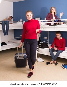 Smiling young female traveler carrying baggage leaving hostel room