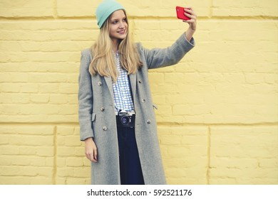 Smiling young female traveller taking selfie using smartphone and internet connection in roaming sharing multimedia files from weekend trip standing on yellow background copy space for advertising