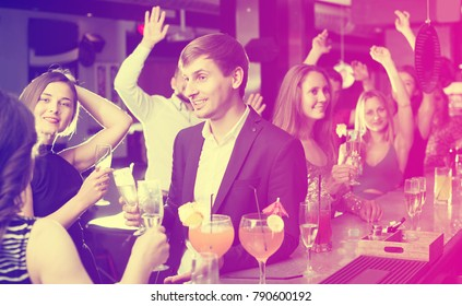 Smiling young females and adult males celebrating corporate in the bar at night