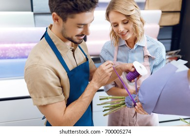 smiling young florists in aprons working with bouquet in flower shop
