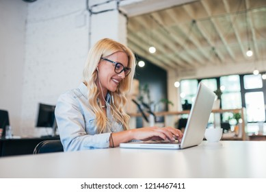 Smiling young freelancer with earphones working on laptop.
