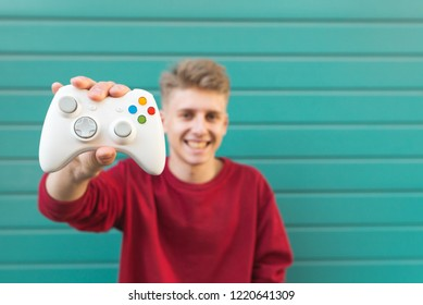 Smiling young gamer with a gamepad in his hand against the background of a turquoise wall, looking into the camera and smiling, shows the joystick in the camera. Gamer concept