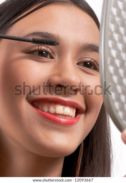 smiling young girl applying a black mascara