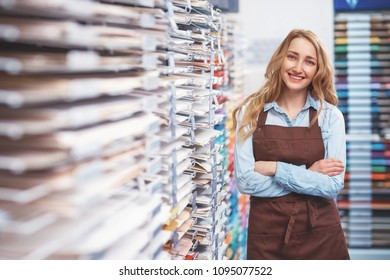 Smiling young girl in an apron in the store