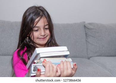 A smiling young girl is carrying a pile of books