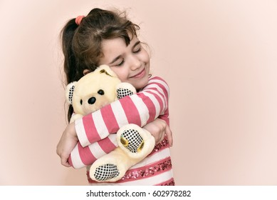 Smiling young girl with closed eyes hugging and playing with teddy bear