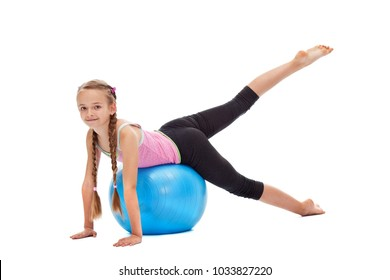 Smiling young girl exercising - using a large gymnastic rubber ball, vitality and strength concept, isolated