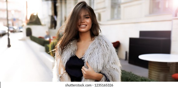 Smiling young girl in fluffy jacket standing on street, catching the last lights of the autumn sun.White teeth, big lips, brunette hair and makeup. Building and bushes on the background. Stylish lady