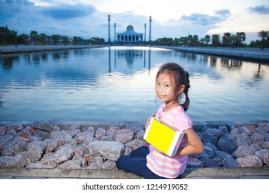 Smiling young girl with holding a empty box on mosque background