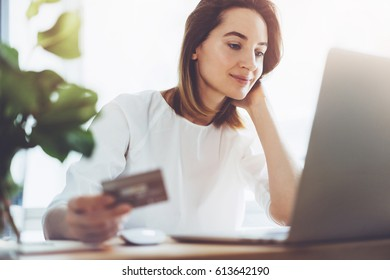 Smiling young girl holding golden credit card on hands and using for online shopping from home, Business woman waiting for confirmation of her online order