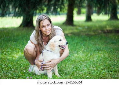 Smiling young girl holding her dog outdoors