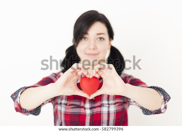 Smiling young girl holding a small red heart and her fingers in the form of heart. Happy first love concept, blurred background.