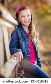 Smiling young girl leaning on fence