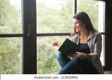 Smiling young girl looking outside the window observing nature or people, distracted from reading interesting book, happy wife excited seeing husband coming home enjoying novel sitting on windowsill