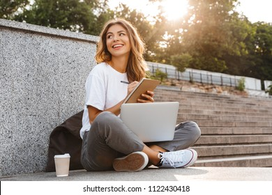 Smiling young girl making notes in notepad while sitting outdoors with laptop computer and coffee cup