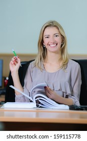 Smiling young girl in the office sitting at a table flipping a book with a pen