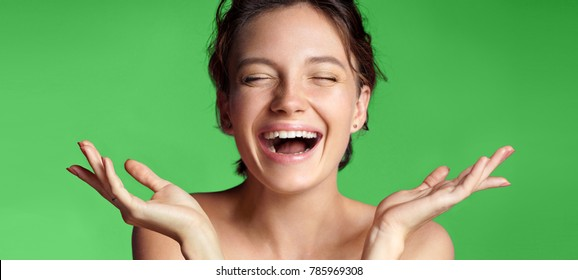 Smiling young girl with perfect skin. Photo of brunette girl showing empty copy space on green background. Youth and Beauty