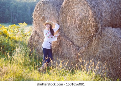 Smiling young girl posing at hay bales. Farm girl wearing blouse, cowboy hat and western boots standing in field. Countryside, farming, agriculture
