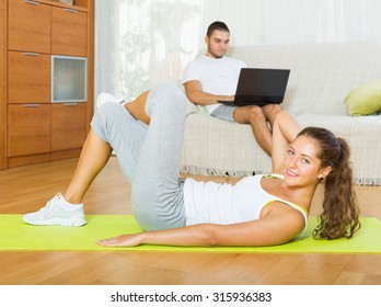 Smiling young girl practicing fitness and her boyfriend resting on couch