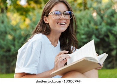 Smiling young girl reading a book while sitting in the park, laughing