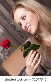 Smiling young girl with a red rose