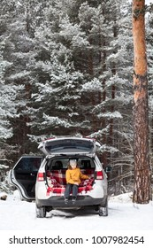 Smiling young girl resting in car back boot for luggage. Winter evergreen woods with huge pines