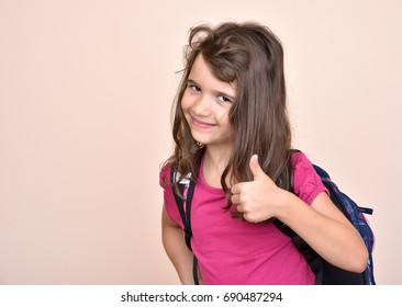 Smiling young girl with school bag showing thumb up