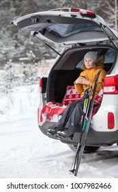 Smiling young girl skier sitting inbuilt compartment for luggage of car and drinking hot tea from cup. Winter woods
