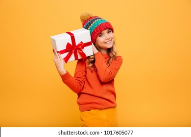 Smiling Young girl in sweater and hat holding gift box and looking at the camera over orange background
