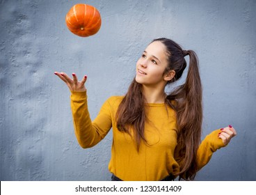 Smiling young girl throwing up orange pumpkin on grunge background, autumn concept
