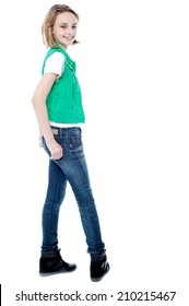 Smiling young girl turning back, hands in pocket