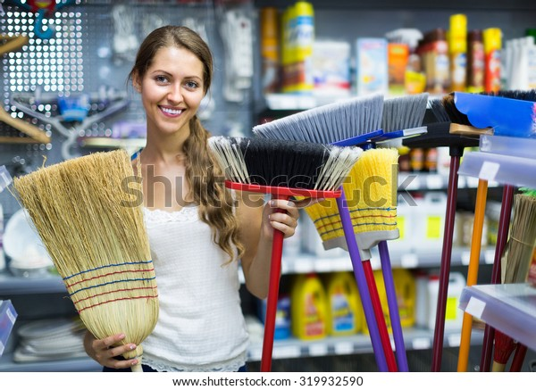 Smiling young girl wants to buy broom at the household store